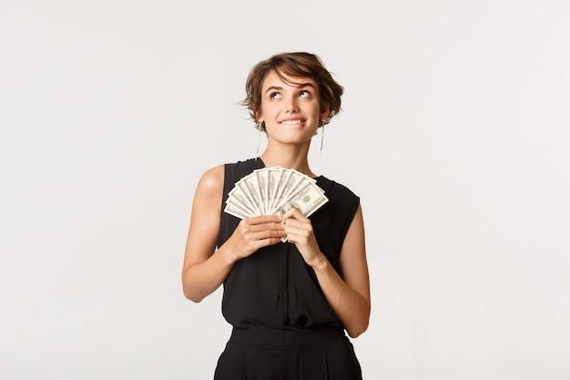 Мечтательная красивая девушка смотрит в левый верхний угол и думает, держа деньги, стоя над белой.