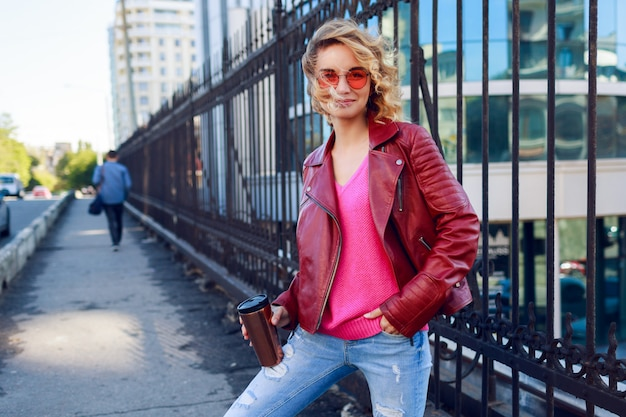 Dreamy blond girl walking the streets, drinking coffee or cappuccino. stylish autumn outfit, leather jacket and knitted sweater. pink sunglasses.