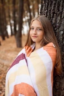 공원에서 나무 근처에 서 있는 줄무늬 격자 무늬에 싸인 꿈꾸는 듯한 금발 소녀