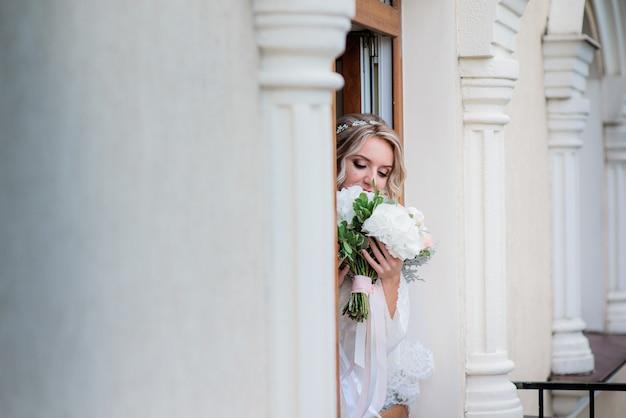 Мечтательная невеста с свадебным букетом стоит за колонной в зале