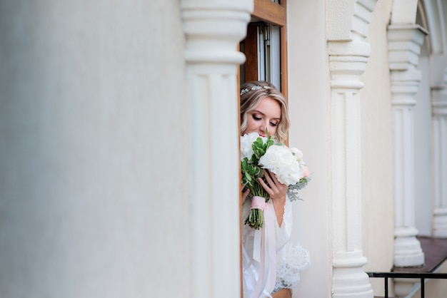 Dreamy bride with wedding bouquet stands behind the column in the hall