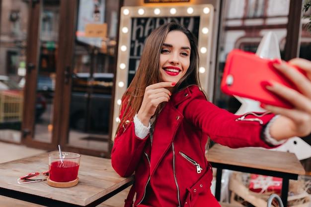Ragazza dai capelli castani sognante utilizza lo smartphone per selfie sullo spazio urbano