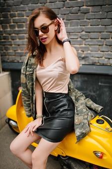 Мечтательная шатенка в наручных часах и модной куртке сидит на желтом скутере после поездки по городу