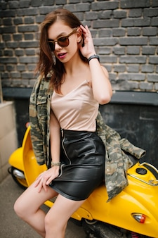 Dreamy brown-haired girl wearing wristwatch and trendy jacket sitting on yellow scooter after ride around city