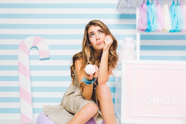 꿈꾸는 갈색 머리 소녀는 줄무늬 벽에 아이스크림을 먹을 가치가 있는지 의심합니다. 과자가 게 옆에 앉아 맛있는 디저트를 손에 들고 사려 깊은 젊은 여자의 초상화.