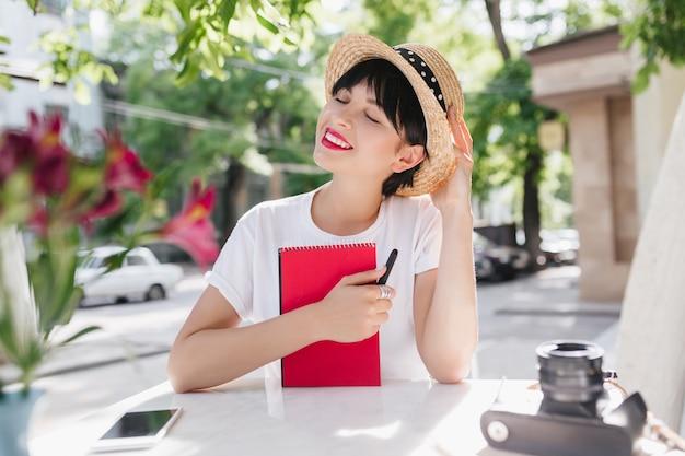 目を閉じて楽しい何かを考えている黒いリボンと麦わら帽子の夢のようなブルネットの女の子