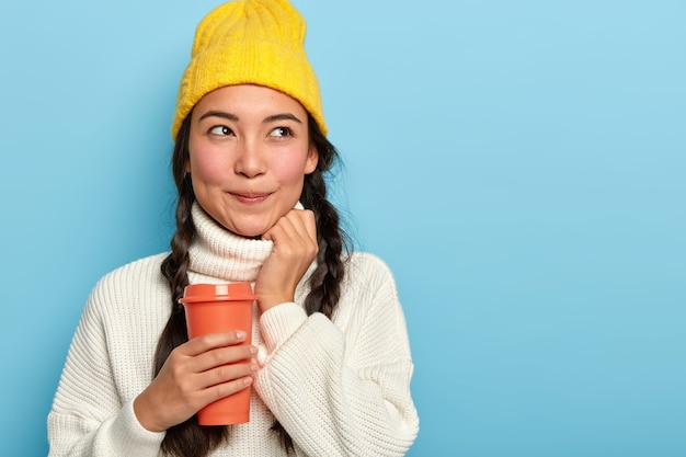Dreamy brunette woman has natural appearance, wears yellow hat and white jumper, holds takeaway coffee, being deep in thoughts