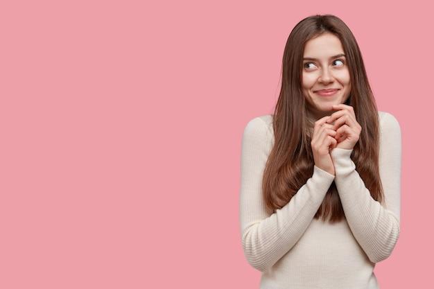 夢のようなブルネットの女性は優しく微笑んで、あごの下で手を一緒に保ち、カジュアルな服を着ています