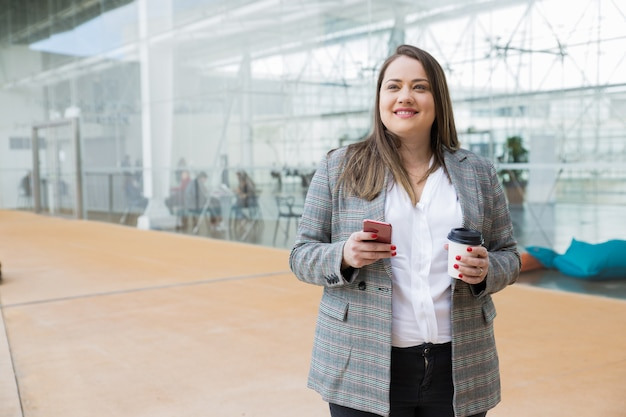 Dreamy business woman holding smartphone and drink outdoors