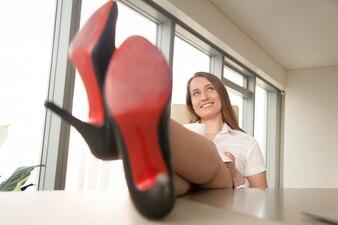 夢のような実業家の仕事でリラックス、コーヒーを飲みながら、机の上の足