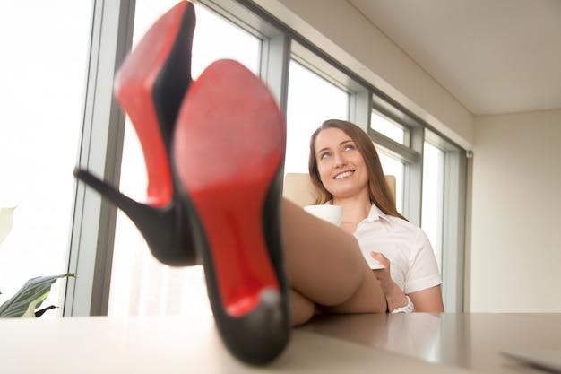 Мечтательная деловая женщина отдыхает на работе, пьет кофе, ноги на столе