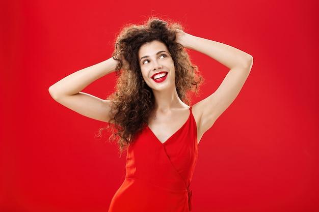 Мечтательная беззаботная молодая европейка с кудрявой прической и трогательной прической с вечерним макияжем довольна результатом после посещения салона, глядя на мечту или воображая идеальное свидание в красном платье.