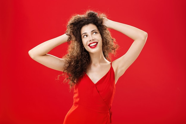 Dreamy carefree young european female with curly hairstyle and evening make-up touching hairstyle pleased with result after visiting salon looking up dreaming or imaging perfect date in red dress.