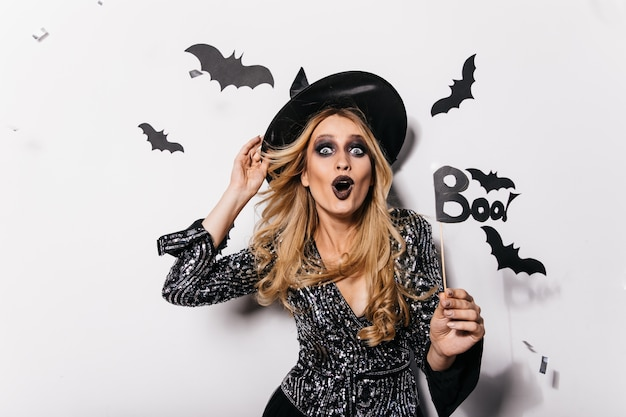 Dreamy caucasian girl in wizard hat expressing surprised emotions. indoor photo of happy european woman in witch attire celebrating halloween.