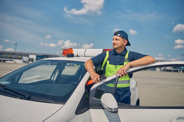 Dreamy caucasian marshaller in his workwear leaning on the open car parked at the aerodrome