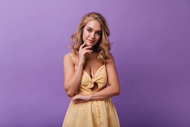 紫の上に立ってカメラを見ている夢のような白人女性。屋内のポートレート撮影を楽しんでいる夏服の素晴らしい女性モデル。