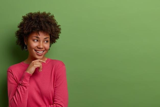 Мечтательная жизнерадостная кудрявая афроамериканка держит руку за подбородок, видит что-то приятное и привлекательное, одетая в розовый джемпер, стоит у зеленой стены, свободное место для вашей рекламы
