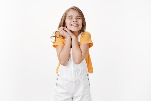 Мечтательная жизнерадостная счастливая маленькая девочка со светлыми волосами, сжимающая руки радостно, не может дождаться выдающегося события, закрывать глаза, мечтательно улыбаясь, чувствуя безмерную радость и счастье, стоять у белой стены