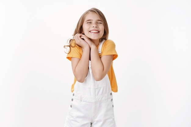 Dreamy cheerful happy little girl with blond hair, clasp hands together joyfully cannot wait outstanding event, close eyes smiling dreamy, feeling overjoy and happiness, stand white wall