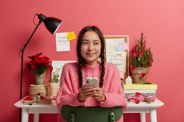 Dreamy cheerful millennial girl sits relaxed against desktop, chats with friends, has work break for sending message, decorates workplace for christmas