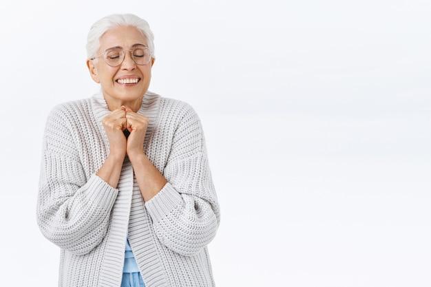 Donna anziana sognante e allegra che prova affetto e gioia mentre ricorda un bel ricordo, stringe le mani vicino al petto, chiude gli occhi e sorride eccitato, i bambini contenti tornano a casa per le vacanze