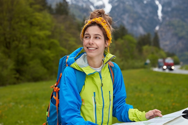 Dreamy cheerful woman dressed in active wear, uses tourist map for finding right route, wears backpack