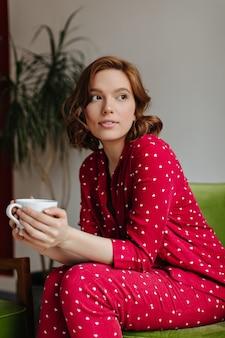 一杯のコーヒーを持って目をそらしている夢のような巻き毛の女性。お茶を飲む赤いパジャマを着た陽気な若い女性の屋内ショット。