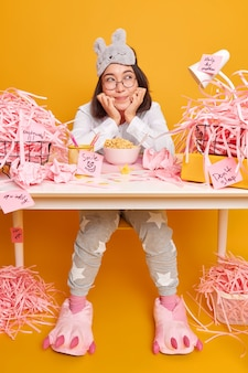 Dreamy cute asian student dressed in soft pajama and sleepmask on forehead has breakfast at workplace enjoys cozy home environment poses at messy desktop with paper rubbish yellow wall