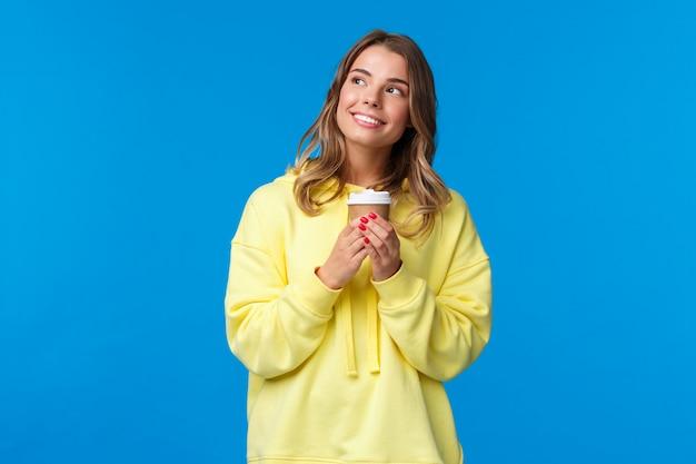 Мечтательная милая белокурая европейская девушка в желтой толстовке смотрит романтично и задумчиво, улыбаясь про себя, представляя что-то каваи, держащее бумажный стаканчик и пьющий кофе,