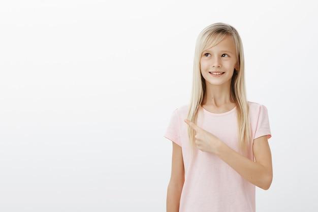左上隅を指す夢のようなかわいい金髪少女満足、イメージングまたは思考