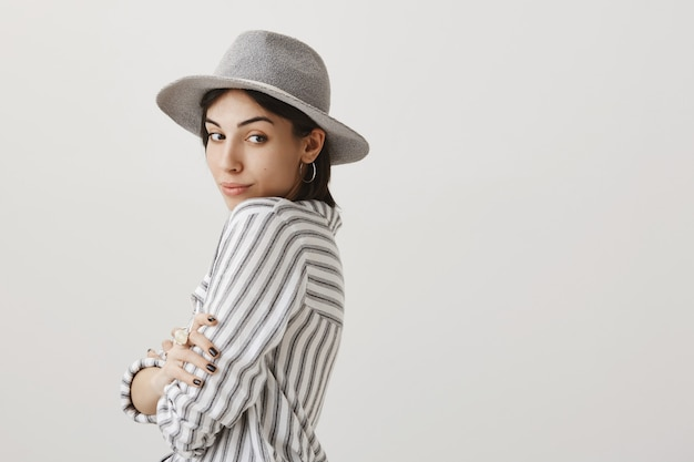 好奇心が強い笑顔で後ろを見て灰色の帽子で夢のようなかわいいブルネットの女性