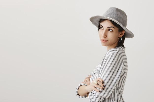 Мечтательная милая девушка в серой шляпе смотрит в левый верхний угол