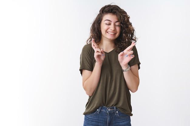 夢のようなかわいい幸運な少女が祈って、奇跡の目を閉じて、広く指を交差させて笑いながら、神に願いを叶えてくれることを願っています。