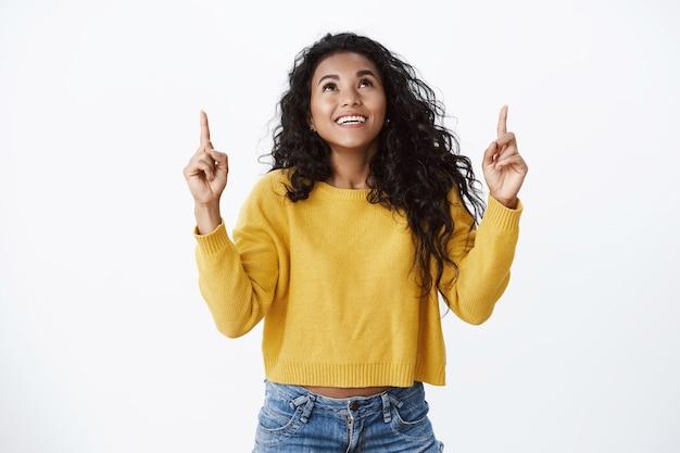 黄色いセーターを着た夢のようなかわいい笑顔のアフリカ系アメリカ人女性が面白がって、見て、指を上に向けて驚いて、素晴らしい機会を見て、のんきに笑って、白い壁