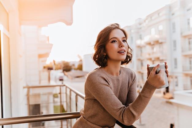 Ragazza sognante dagli occhi scuri che beve il tè al balcone. foto del modello femminile ben vestito caucasico che tiene la tazza di caffè.