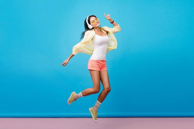 カジュアルなカラフルな服装で踊る夢のような黒髪のラテン女性。青い壁の部屋でジャンプする幸せな表情を持つロマンチックな若い女性の屋内写真。