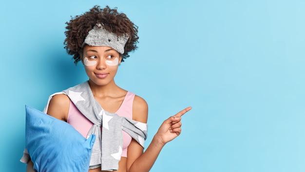 Una donna sognante dalla pelle scura con i capelli ricci applica pastiglie di collagene sotto gli occhi per ridurre il gonfiore dopo aver dormito
