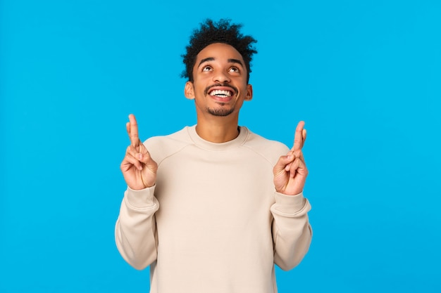 Мечтательный взволнованный и счастливый молодой человек созерцает чудесный фейерверк на новогоднем празднике, наблюдая за развлекательной сценой. привлекательный афро-американский парень, глядя и указывая вверх, счастливо улыбаясь