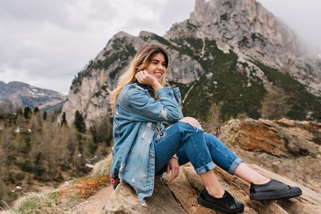 Мечтательная светловолосая девушка в джинсовой одежде отдыхает на скале после тяжелого лазания и позирует, касаясь ее лица