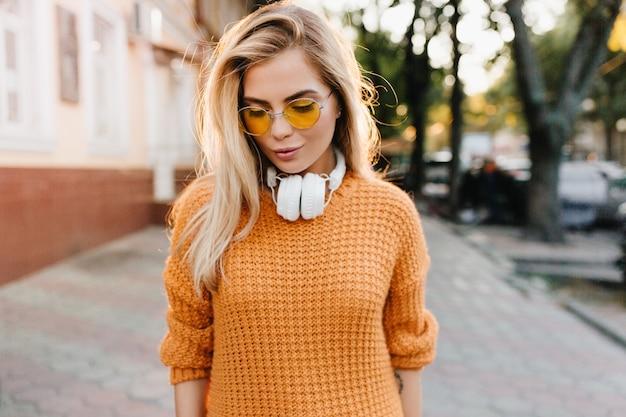 Мечтательная светловолосая девушка в желтом свитере смотрит вниз, стоя на размытом уличном фоне