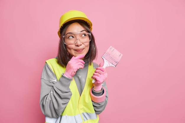 Dreamy female building contractor makes plans thinks about new decor of apartment going to paint walls wears safety glasses helmet uniform holds painting brush