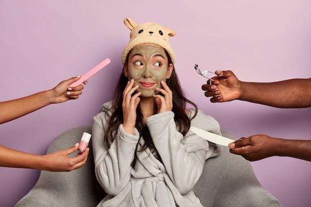 Il modello femminile sognante tocca il viso, attende un bell'effetto dopo la maschera all'argilla