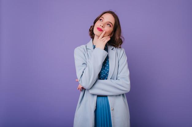Modello femminile sognante in vestito blu alla moda in posa. tiro al coperto della signora riccia caucasica felice indossa il cappotto.