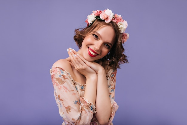 Мечтательная женская модель с красивой улыбкой позирует. красивая кудрявая девушка с розами в волосах.