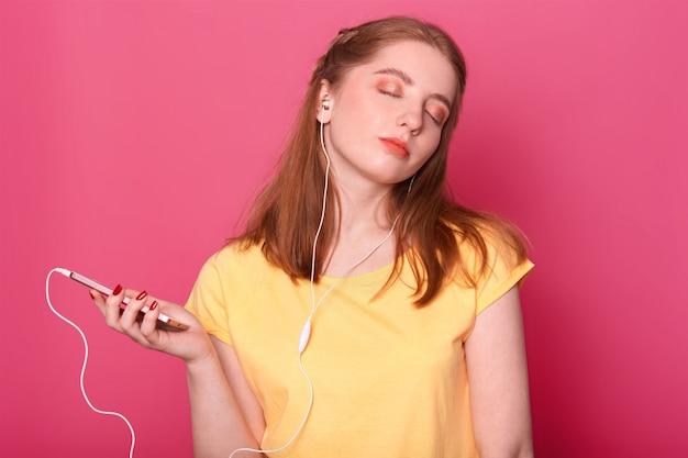 Donna da sogno con espressione pensosa e occhi chiusi, ha le cuffie moderne, ascolta la musica, trascorre il tempo libero da sola, posa sul rosa con spazio vuoto per la tua pubblicità.