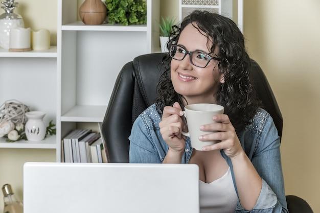 Dreamy freelancer resting with mug of hot drink