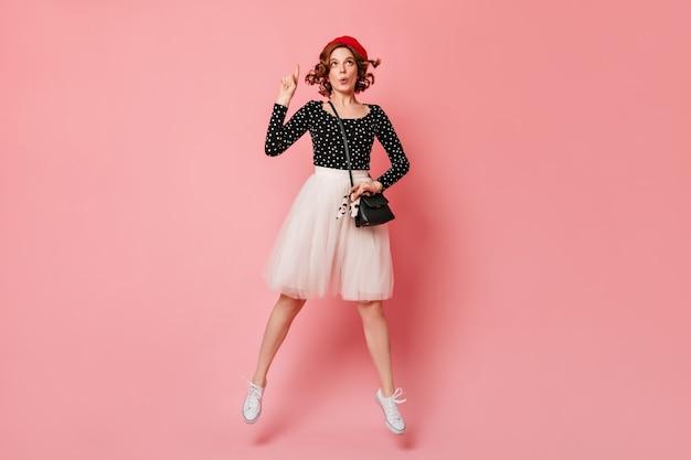 指で指している夢のようなフランスの女の子。ピンクの背景に身振りで示すベレー帽の素敵な女性のスタジオショット。