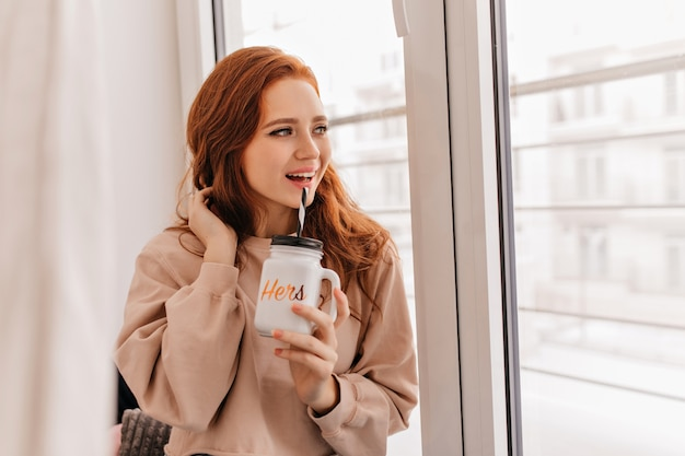 窓の横でお茶を飲む夢のような生姜の女の子。家で休んでいるリラックスした若い女性の屋内写真。