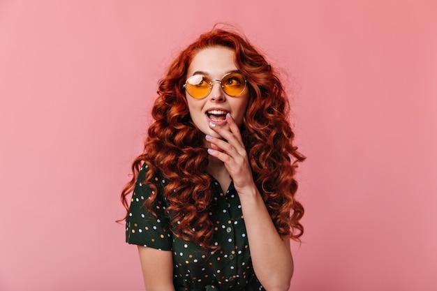 口を開けて目をそらしている夢のような生姜の女の子。ピンクの背景にポーズをとるサングラスの感情的な若い女性のスタジオショット。
