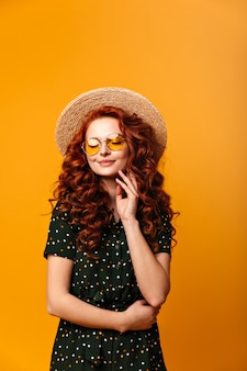 Dreamy ginger girl posing with closed eyes. studio shot of amazing caucasian woman in straw hat isolated on yellow background.